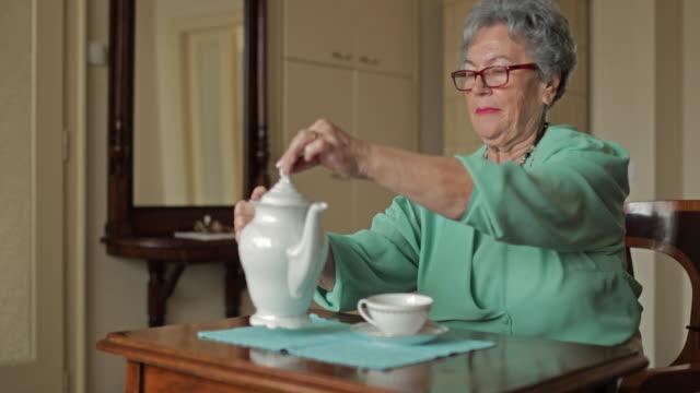 Gelukkig oude vrouw genieten in afternoontea thuis en te zwaaien naar de camera.