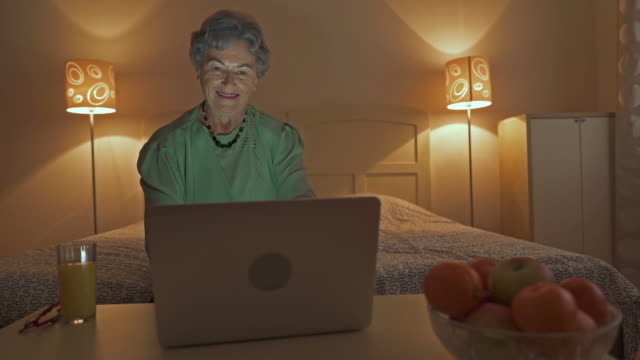 Happy old woman reading an e-mail on laptop and celebrating good news.