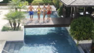 Happy people jumping into pool