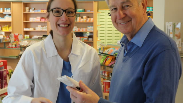 Happy Pharmacist And Senior Man In Store
