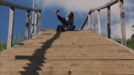Happy pregnant female making selfie agains blue sky on stairs