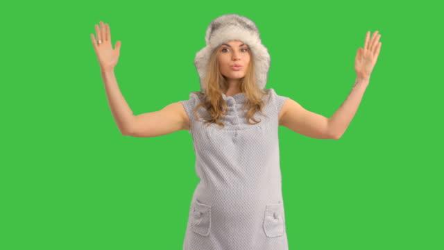 Glückliche schwangere Frau in Hut präsentiert Textfreiraum auf grünem Hintergrund
