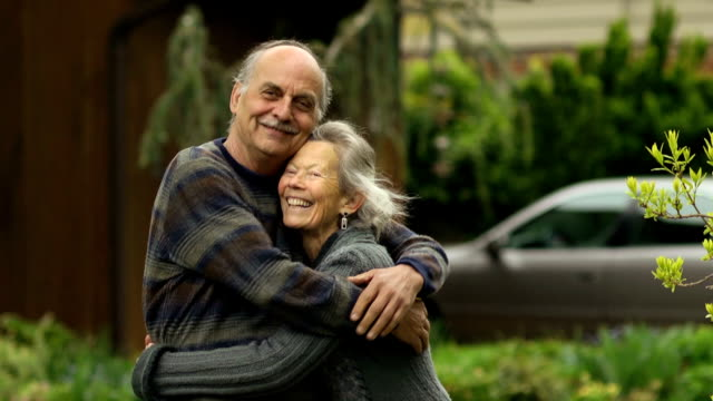 Happy Senior Couple Embracing in Front of Home