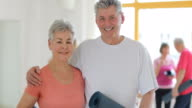 Happy senior couple holding exercise mat in gym