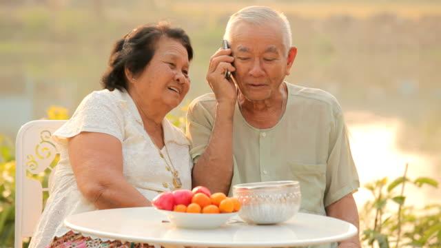 Felice coppia senior parla su un telefono cellulare