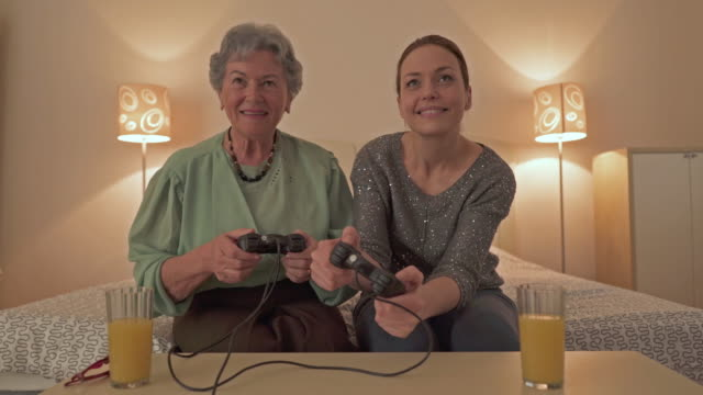 Happy senior woman and her adult daughter playing video games at home.