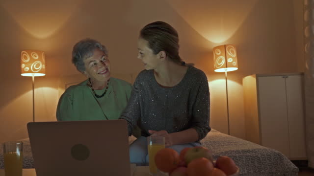 Happy senior woman and her daughter using laptop and communicating with someone through the Internet.