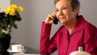 Glückliche Senior Frau spricht über Dokumente am Telefon