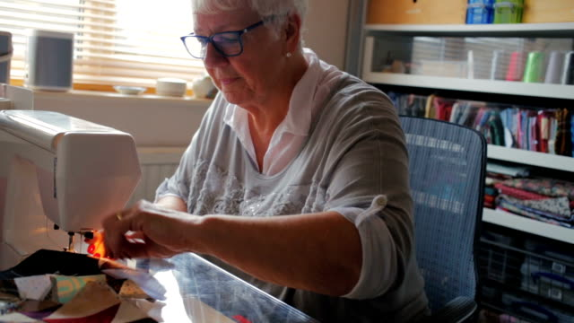 Happy Senior Woman Doing a Hobby Sewing A Quilt