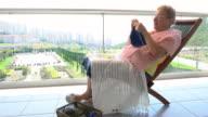 Happy senior woman knitting  in nursing home.
