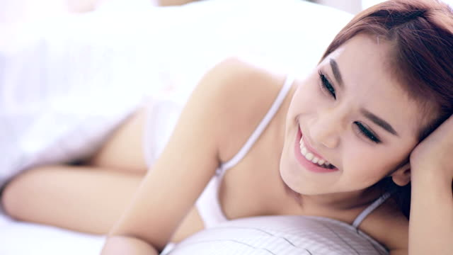 Happy smiling beautiful woman awaking with cup of coffee at bedroom