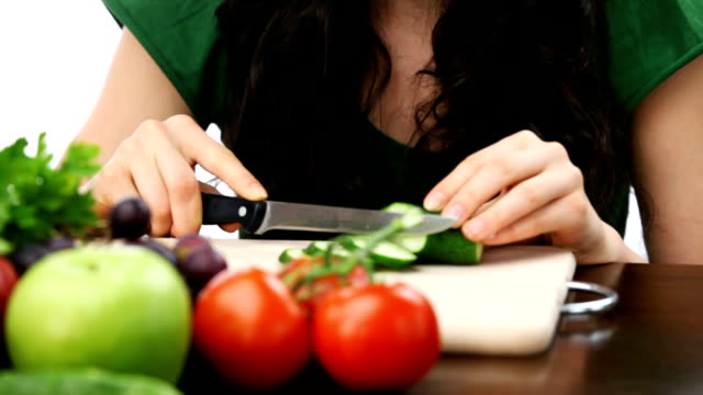 HD: Happy smiling woman making vegetable salad, on white
