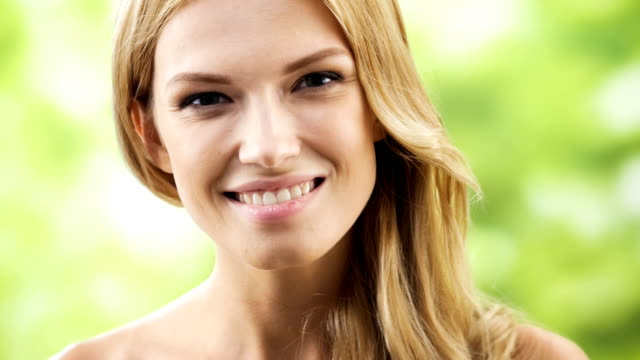 Happy smiling woman touching skin or applying creme, outdoors