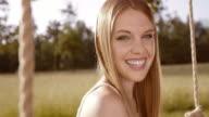 SLO MO glada leende ung kvinna på en gunga