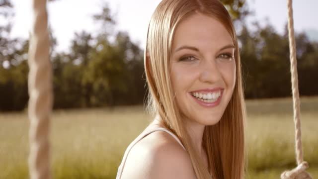 SLO MO glücklich lächelnde Junge Frau auf Schaukel