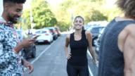 Happy sporty woman talking to friends on sidewalk