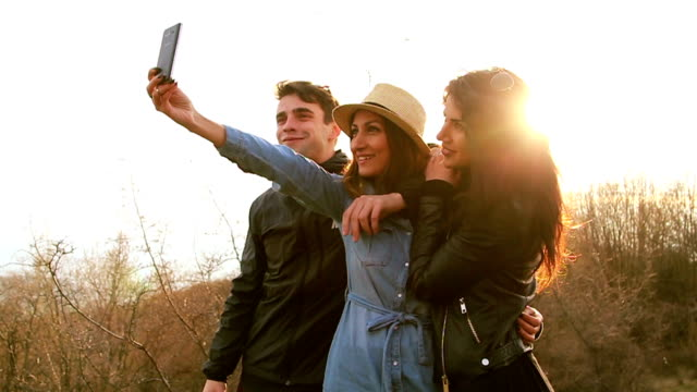 Happy three friends taking a photo of themselves