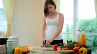 Happy woman cooking vegetables green salad