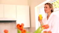 Happy woman drinking orange juice in the morning