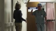 SLO MO MS Happy woman embracing surgeon in hospital corridor / Payson, Utah, USA