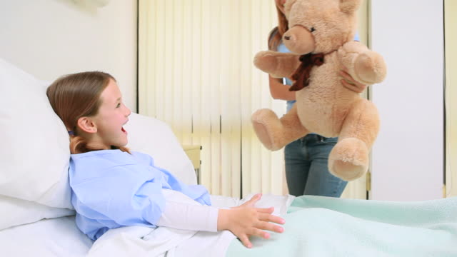 Happy woman giving a teddy bear to a girl in a bed