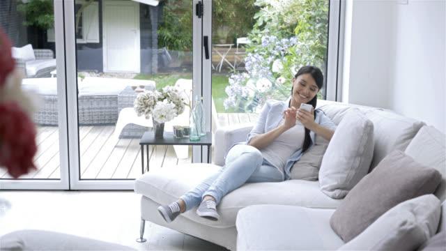 Gelukkige vrouw zittend op de Bank met haar smartphone