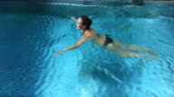 Happy woman swimming in swimming pool during weekend days of relax and spa in a luxury place during travel vacations.