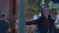 Happy woman swings around light pole on Las Vegas street corner at night.