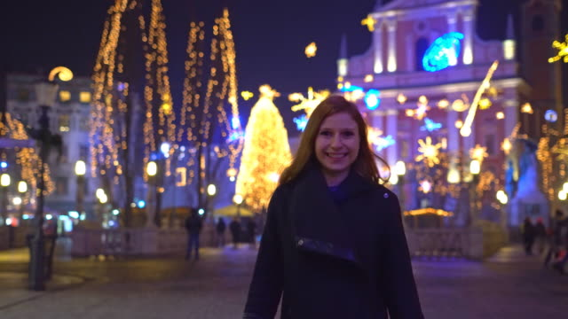 Happy woman walking through decorated city during christmas holidays