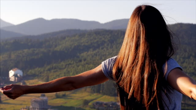 Happy woman whirling at sunset in mountains