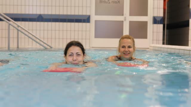 Gelukkig vrouwen houden van drijvers tijdens het zwemmen in zwembad