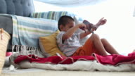 Happy young boy in home made tent playing with toy dinosaur.