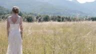 Happy young bride in a field, looking over shoulder