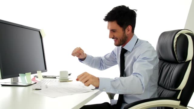 Happy young businessman dancing in his office