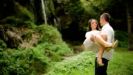 Happy Young Couple Playing in Front of Waterfall