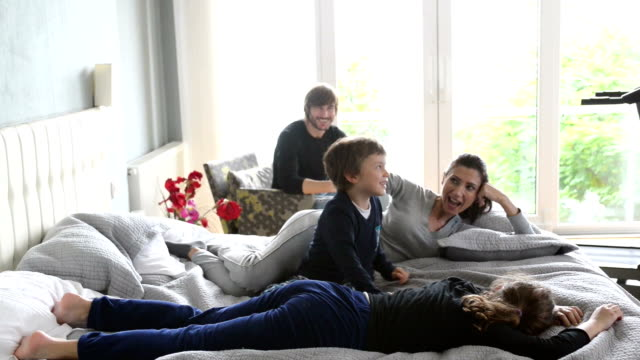 Happy young family having fun together in bed