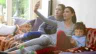 Happy young family taking selfies with her smartphone in home