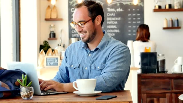 Happy young Hispanic man smiles while using computer in coffee shop