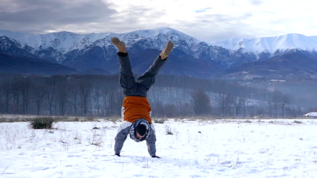 Happy young man doing cartwheel on snow - slowmotion