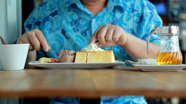 Glücklicher junger Mann Essen Kuchen im Café