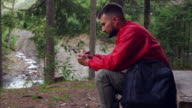 Happy young man using smartphone in nature