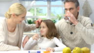 Happy young parents plays with daughter in brightly lit kitchen.
