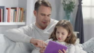 Happy young parents plays with daughter, using new technology in living room