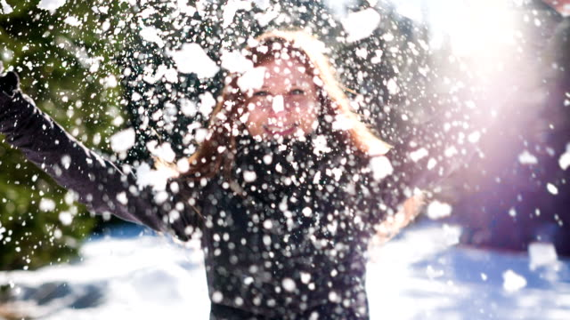 Happy young woman crushing a snowball in the air