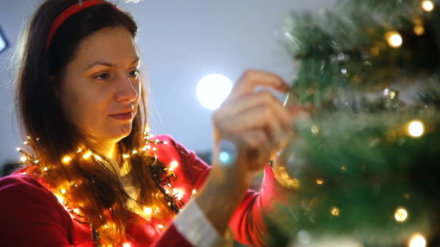 Happy young woman decorating christmas tree at home