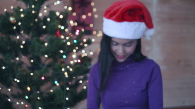 Happy young woman holding christmas present box, Blurred person.