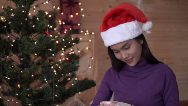 Happy young woman holding christmas present box.