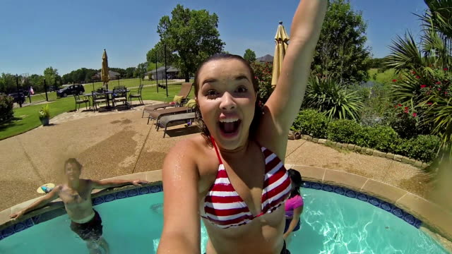 Happy young woman jumps into swimming pool and swims underwater