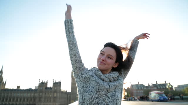 HANDHELD CLOSE UP smiling young woman raises her hands in the air and spins around near Big Ben and Parliament at sunset in London
