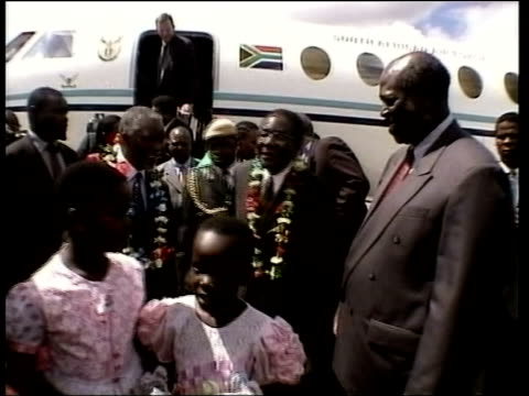 Harare South African President Thabo Mbeki greeted from plane by Mugabe on visit to Zimbabwe GV People in traditional costume dancing in welcome...